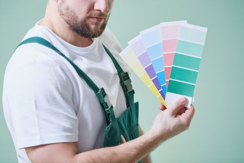 man holding interior paint color swatches